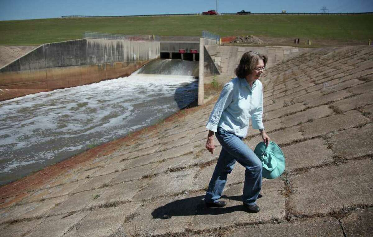 Evelyn Merz, of the Sierra Club, walks the banks of the dam at Addicks Reservoir on the south side of the dam, which releases water into Buffalo Bayou in Houston. The extended development of the Katy Prairie due to the planned extension of Grand Parkway has Merz and others wondering if the dam can continue to protect the city from flooding, which it has been doing for the last six decades.