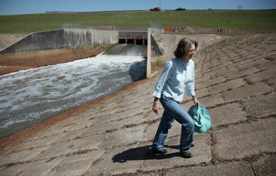 Evelyn Merz, of the Sierra Club, walks the banks of the dam at Addicks Reservoir on the south side of the dam, which releases water into Buffalo Bayou in Houston. Click the gallery to learn more about how Texas dams measure up. Photo: Mayra Beltran / © 2011 Houston Chronicle