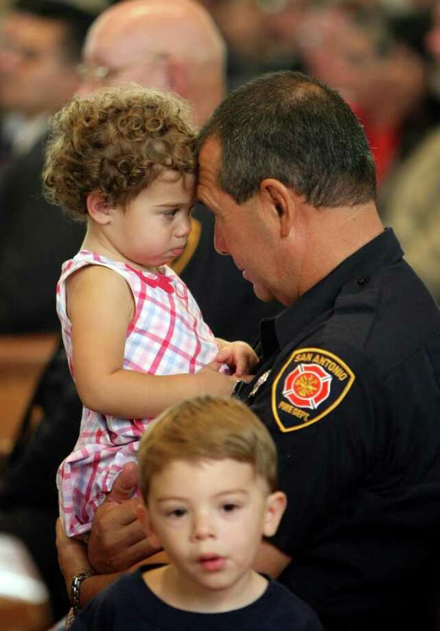 San Antonio firefighter Michael Puzon talks with his daughter, Kaitlyn as his son, Dalton, sits next to them during the the Archdiocese of San Antonio's annual Blue Mass, or the Feast of Archangels, which thanks local law enforcement officers for their service.As originally published, this story contained an error. Photo: HELEN L. MONTOYA, San Antonio Express-News / SAN ANTONIO EXPRESS-NEWS