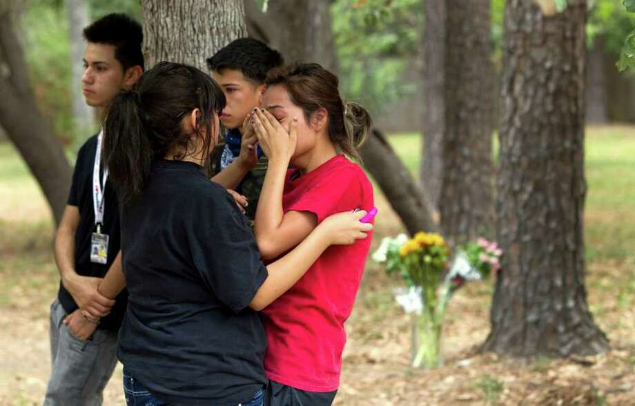 Sofia Garcia, left, comforts Luz Rico, as they stand near the scene of a fatal car accident that claimed the lives of three teenagers in Porter. The three teens died Wednesday when their car struck a tree and flipped over along Sorters Road near Plantation Estates, officials said. Two others were injured in the crash. Photo: Brett Coomer, Houston Chronicle / © 2011 Houston Chronicle