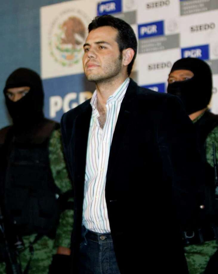 Military officers escort alleged drug trafficker Vicente Zambada during his presentation to the media in Mexico City onMarch 19, 2009. Vicente Zambada, arrested Wednesday in a upscale neighborhood in Mexico City, is the son of Mexican drug lord Ismael Zambada, head of the Sinaloa cartel. Photo: Eduardo Verdugo / AP