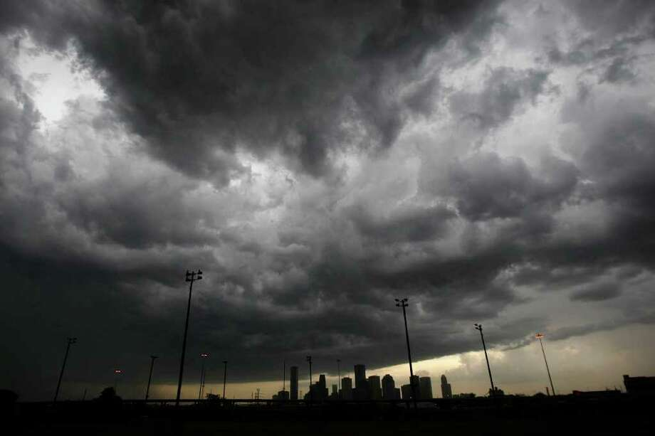 As seen from Stude Park, downtown Houston is silhouetted by a clear sky as storm clouds move in from the north to the south Thursday, Sept. 29, 2011. Photo: Johnny Hanson, Houston Chronicle / © 2011 Houston Chronicle