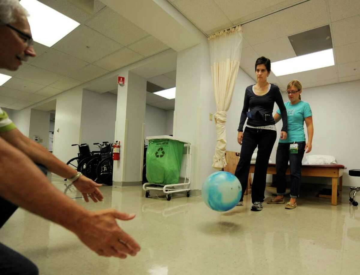 Jennifer Lasher Tinsmon, center is assisted with her physical therapy by Physical Therapist Brigid Kilroy, right and Gary Smith, right at the Sunnyview Rehabilitation Center in Schenectady, N.Y. September 23, 2011. (Skip Dickstein/Times Union)