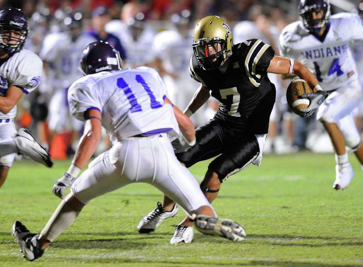 Nederland's Ryan Brady slips past PN-G's Jacob Lynch for a short gain during 2009's Mid-County Madness matchup at Bulldog Stadium. Nederland won 41-21. Guiseppe Barranco/The Enterprise