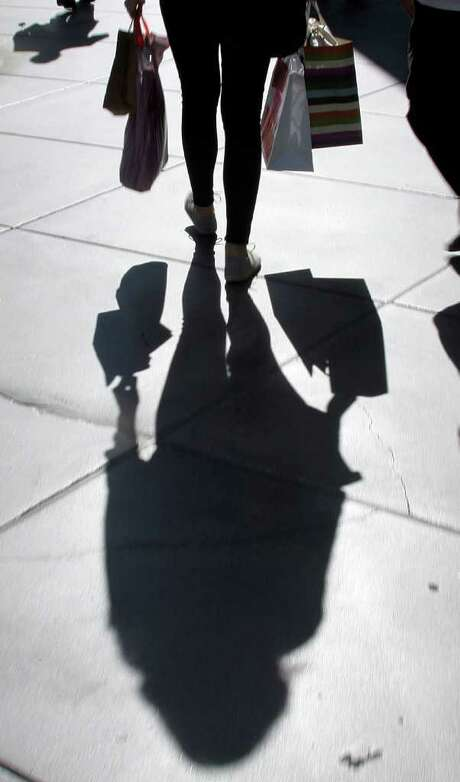 REED SAXON : ASSOCIATED PRESS SHADOWED: A shopper carries bags at a Los Angeles mall this week. The Commerce Department said personal income fell 0.1 percent from July to August. Photo: Reed Saxon / AP