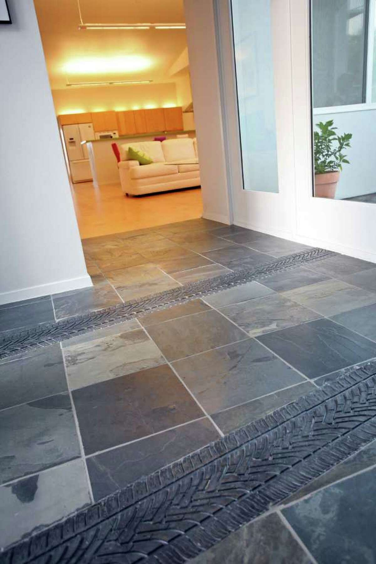 Tile tire tracks add interest to the slate floor in the entry, an idea from a magazine.