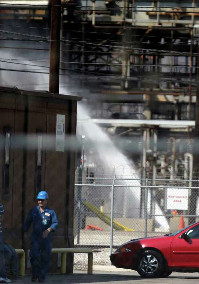 A plant worker walks past a section of the plant being hosed down after a fire at the Pasadena Refining facility on the 100 block of Red Bluff Rd. Friday, Sept. 30, 2011, in Pasadena. Photo: Johnny Hanson, Houston Chronicle / © 2011 Houston Chronicle