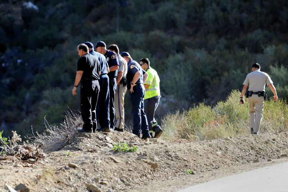 CHILDREN SEARCHED: California Highway patrol officers investigate the scene of the crash that seriously injured David Lavau, 68, who survived a 200-foot plunge. Photo: Gus Ruelas / FR157633 AP