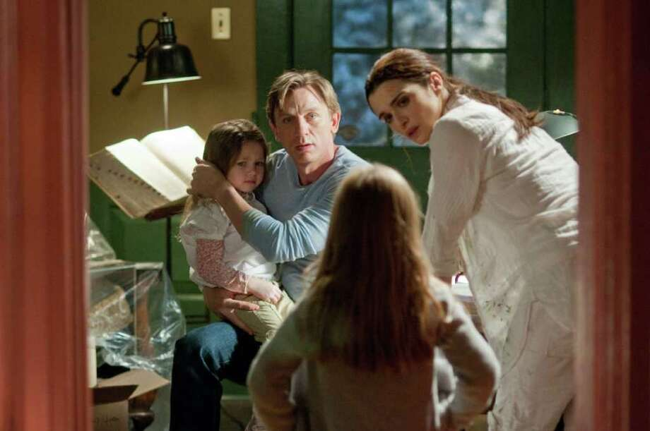 In one of their films, Will Atenton (Daniel Craig) and Libby (Rachel Weisz) console children in 'Dream House,' a suspense thriller about a family that unknowingly moves into a home where several grisly murders were committed...only to find themselves the killer's next target. Photo: Photo Credit:  George Kraychyk /