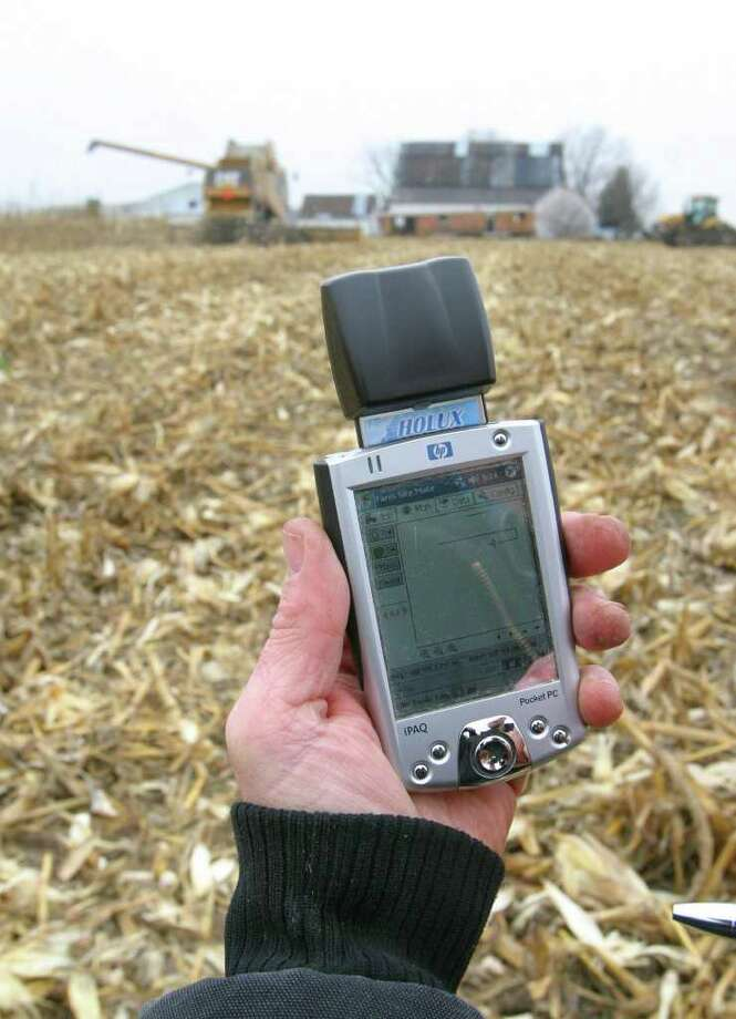 DANIEL MILLER : ASSOCIATED PRESS FARM AID: Brian Watkins uses a device with a GPS receiver to create maps to record different seed and fertilizer combinations in his Kenton, Ohio, farm fields. Some farmers fear a new network will interfere with GPS signals. Photo: DANIEL MILLER / AP
