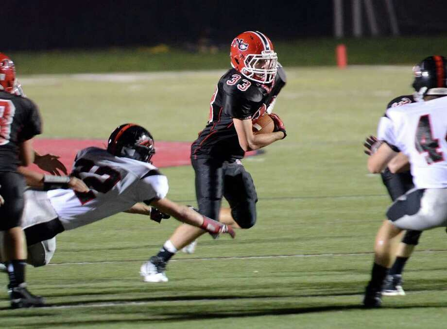 New Canaan's #33 Louis Hagopian breaks free as New Canaan High School hosts Fairfield Warde High School in varsity football action in New Canaan, CT on Friday, September 30, 2011. Photo: Shelley Cryan / Shelley Cryan freelance; Stamford Advocate freelance