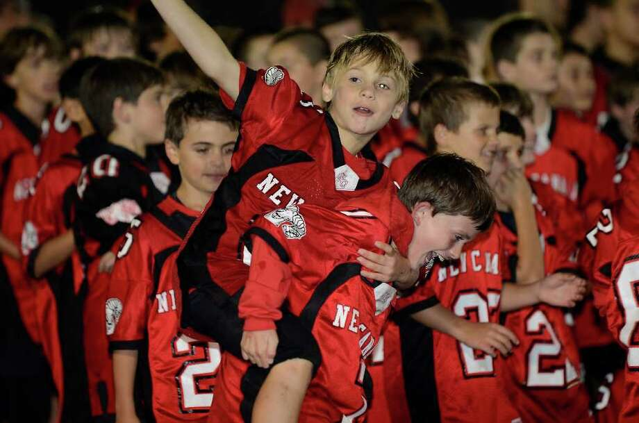 Xander Arnone, 9 (waving) and Colbey Gardiner, 9, of the New Canaan youth football league, take to the field at halftime as New Canaan High School hosts Fairfield Warde High School in varsity football action in New Canaan, CT on Friday, September 30, 2011. Photo: Shelley Cryan / Shelley Cryan freelance; Stamford Advocate freelance