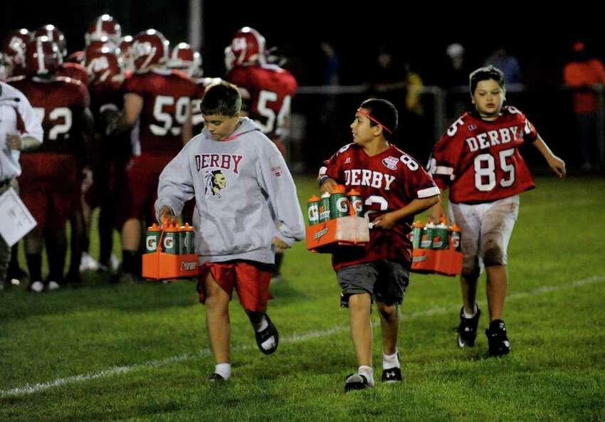 Derby waterboys John Benanto, 11, left, Jordan Stefancin, 12, center, and Anthony DiMartino, 12, right, rush back to the sidelines during the Derby Vs Ansonia football game in Derby, Conn. on Friday September 30, 2011.