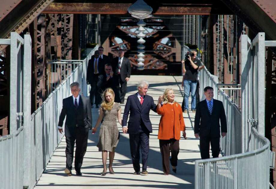 Arkansas Governor Mike Beebe, left, Chelsea Clinton, second from left, Former President Bill Clinton, center, Secretary of State Hillary Rodham Clinton, second from right, and U.S. Assistant Secretary of Commerce for Economic Development John Fernandez, right, cross a new pedestrian bridge in Little Rock, Ark. Friday Sept. 30, 2011. Former president Clinton was in town to dedicate the bridge located adjacent to his presidential library. Photo: Brian Chilson, Associated Press / FR117506 AP