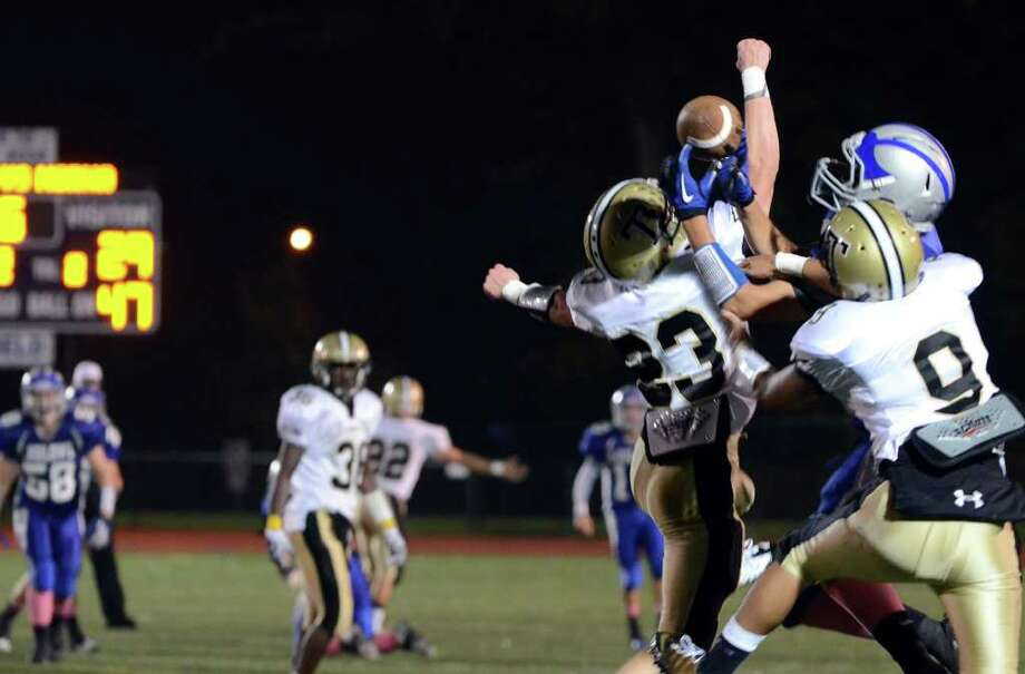 Trumbull's Michael Uus and Matt Nakano break up a pass intended for Ludlowe during the football game against Fairfield Ludlowe at Fairfield Ludlowe High School on Friday, Sept. 30, 2011. Photo: Amy Mortensen / Connecticut Post Freelance