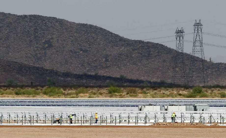 Workers continue to build rows of solar panels at a Mesquite Solar 1 facility under construction Friday, Sept. 30, 2011, in Arlington, Ariz.  The new solar facility is part of a $1 billion Energy Department loan guarantee, of which $337 million is going to Mesquite Solar 1, for the 150 megawatt solar facility. (AP Photo/Ross D. Franklin) Photo: Ross D. Franklin / AP