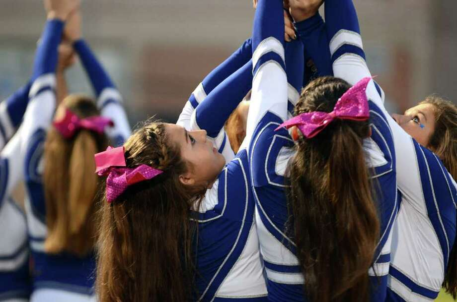 A Fairfield Ludlowe cheerleaders perform a stunt on the sideline during the football game against Trumbull at Fairfield Ludlowe High School on Friday, Sept. 30, 2011. Photo: Amy Mortensen / Connecticut Post Freelance