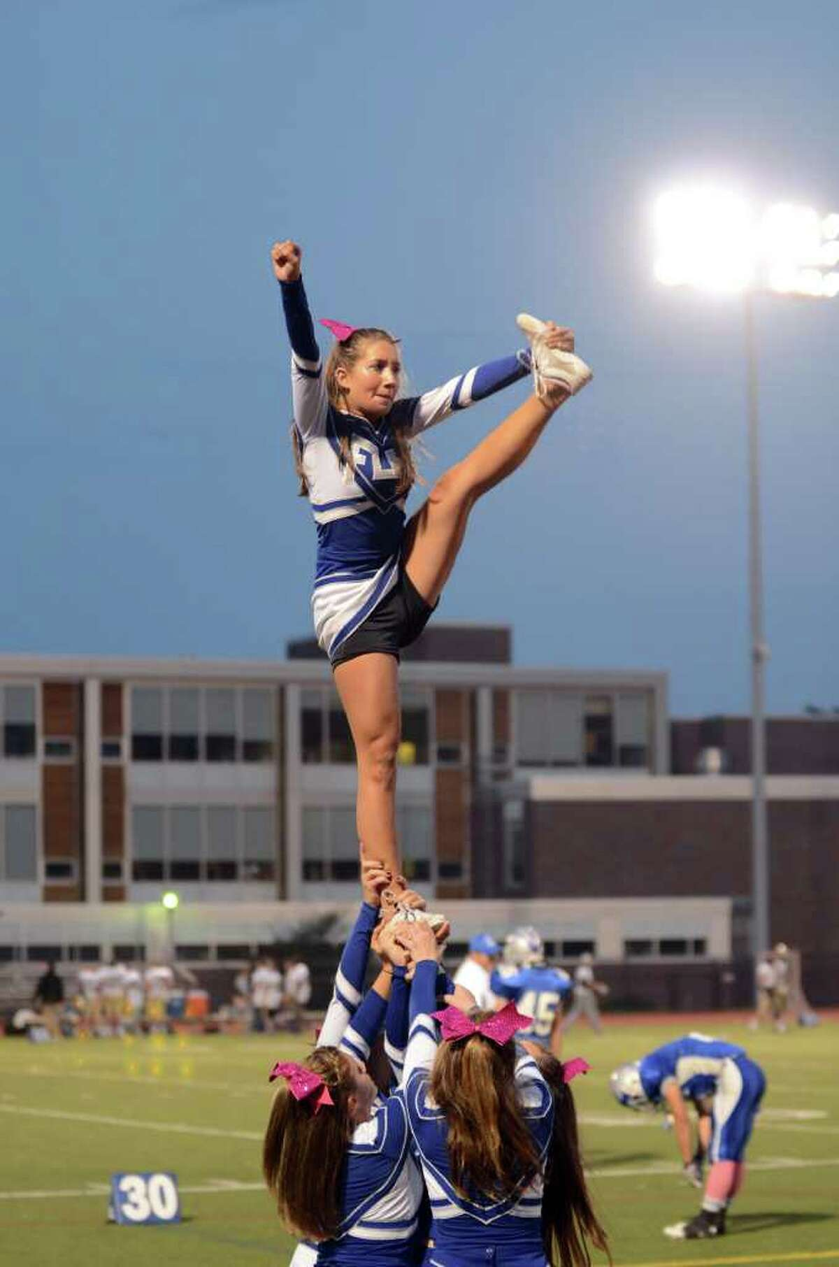 Fairfield Ludlowe cheerleaders perform on the sideline during the football game against Trumbull at Fairfield Ludlowe High School on Friday, Sept. 30, 2011.