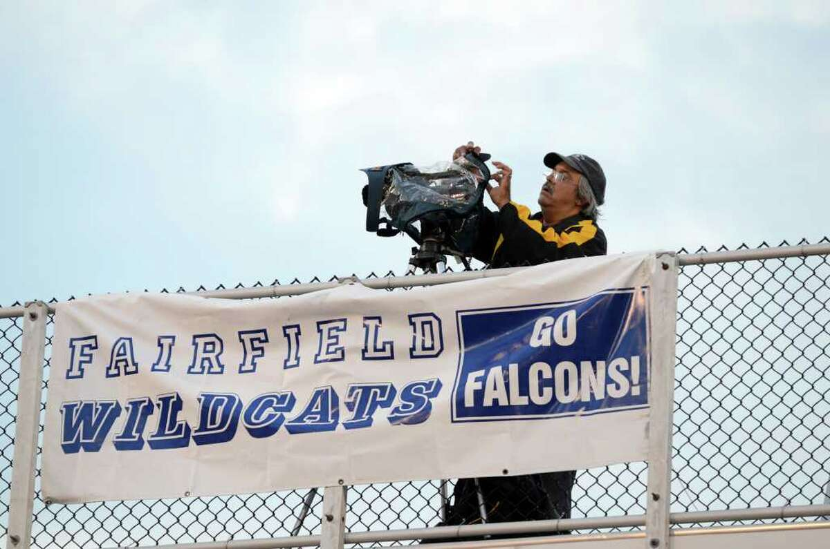 A cameraman places his rain gear on his camera during the Fairfield Ludlowe football game against Trumbull at Fairfield Ludlowe High School on Friday, Sept. 30, 2011.