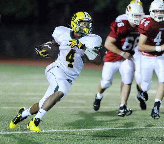 New London High School running back Kyle McKinnon, # 4, on one of his 28 runs during High School football game between New London High School and Greenwich High School at Greenwich, Friday night, Sept. 30, 2011.  Mckinnon rushed for a total of 236 yards as the Whalers defeated the Cardinals 51-33.  Trailing the play for Greenwich are Robert Gelcius, # 66, and Patrick Callahan, #44. Photo: Bob Luckey / Greenwich Time
