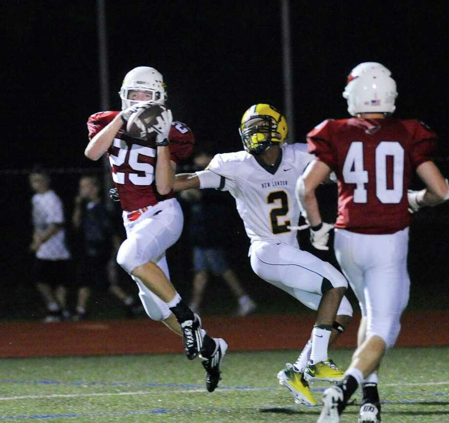 Ryan Kelly, # 25 of Greenwich High School steps in front of Doug Henton, # 2 of New London High School to intercept a pass that he ran back more than 100 yards for a touchdown during High School football game between New London High School and Greenwich High School at Greenwich, Friday night, Sept. 30, 2011.  At right for GHS is Taylor Lomstead.  The Whalers defeated the Cardinals 51-33. Photo: Bob Luckey / Greenwich Time