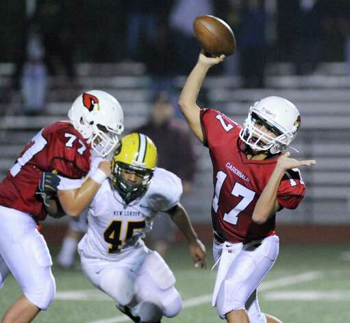 Greenwich High School quarterback Jose Melo, # 17, throws while getting blocking from teammate Damian Orellano, # 77 during High School football game between New London High School and Greenwich High School at Greenwich, Friday night, Sept. 30, 2011.  New London defeated Greenwich 51-33.  Getting blocked on the play is Shaquan Green of New London High School. Photo: Bob Luckey / Greenwich Time