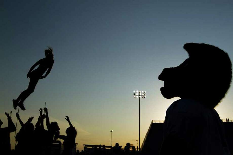 "Friendswood Mustangs mascot ""Mighty"" watches the team's cheerleaders warm up before a high school football game against Dawson. Photo: Smiley N. Pool, Houston Chronicle / © 2011  Houston Chronicle"