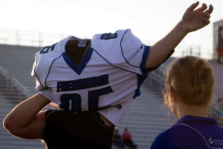 Friendswood's Trevor Stevens puts on his pads and jersey before a high school football game against Dawson. Photo: Smiley N. Pool, Houston Chronicle / © 2011  Houston Chronicle