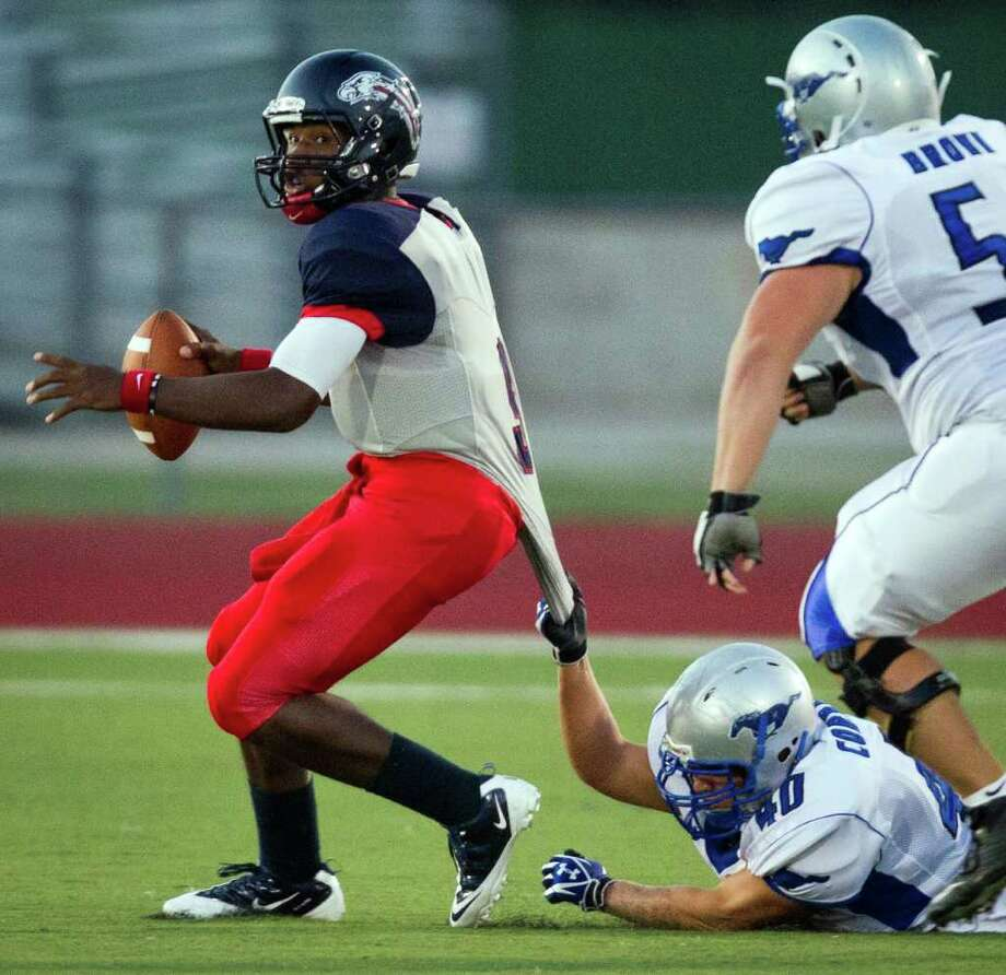 Dawson quarterback Garry Kimble (9) tries to escape the grasp of Friendswood defensive lineman Grayson Correa (40) during the first quarter. Photo: Smiley N. Pool, Houston Chronicle / © 2011  Houston Chronicle