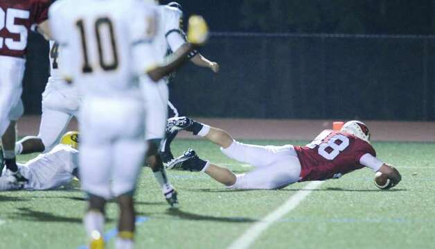Greenwich High School running back Shane Nastahowski, # 48, dives across the goal line to score a first quarter touchdown during High School football game between New London High School and Greenwich High School at Greenwich, Friday night, Sept. 30, 2011.  New London defeated Greenwich 51-33.  At right is Khaleed Fields, # 10 of New London High School. Photo: Bob Luckey / Greenwich Time