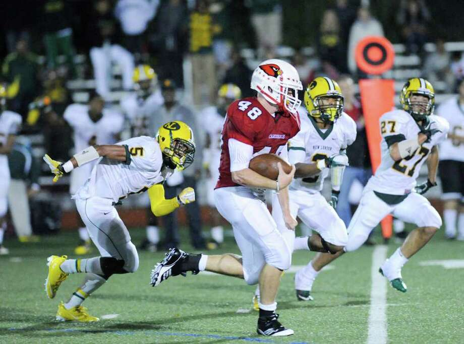 GHS running back Shane Nastahowski, # 48, outruns New London High School players, Jevon Elmore, # 5, Doug Henton, # 2 and Caleb Camacho, # 27, during High School football game between New London High School and Greenwich High School at Greenwich, Friday night, Sept. 30, 2011.  New London defeated Greenwich 51-33. Photo: Bob Luckey / Greenwich Time