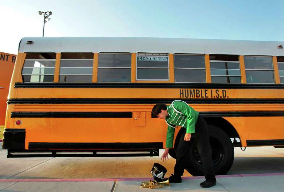 Kingwood Park High School band member Brandon Fulcher picks up his hat and trumpet before the start of a football game against Summer Creek High School at Turner Stadium. Photo: Cody Duty, Houston Chronicle / © 2011 Houston Chronicle