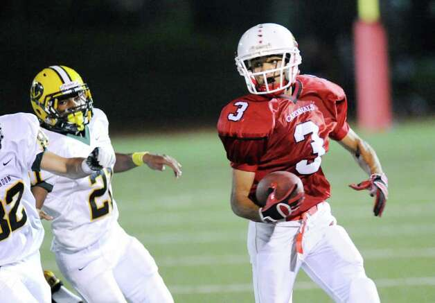 Greenwich High School receiver Joel Arroyo, # 3, out-runs a pair of New London defenders on a catch during football game between New London High School and Greenwich High School at Greenwich, Friday night, Sept. 30, 2011.  New London defeated Greenwich 51-33. Photo: Bob Luckey / Greenwich Time