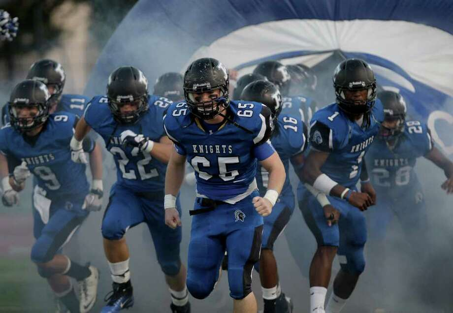 Carter Mizell (65) and the Episcopal Knights run out of the tunnel before playing against Kinkaid. Photo: For The Chronicle: Thomas B. She