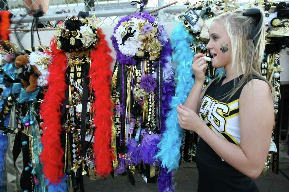 Klein Oak cheerleader Madie Willey applies lip balm in front of a row of homecoming mums before the Panthers' game against Klein Forest. Photo: Eric Christian Smith, For The Chronicle