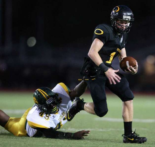 Klein Oak's Connor McQueen (right) scampers past Klein Forest's Tyree Gray during the first half.