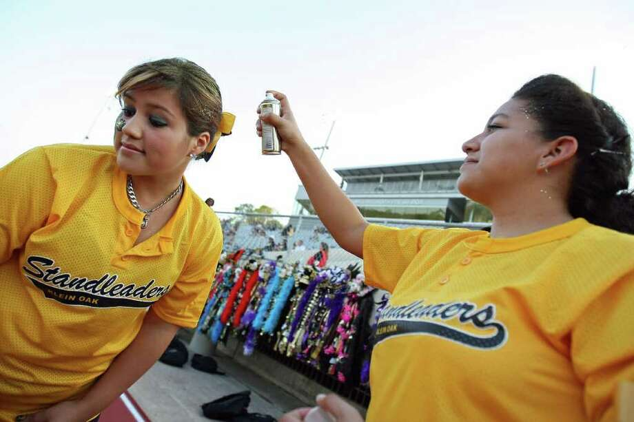 Stephanie Melendez sprays glitter on fellow Klein Oak Standleader Samantha Beasley before the Panthers' game against Klein Forest. Photo: Eric Christian Smith, For The Chronicle