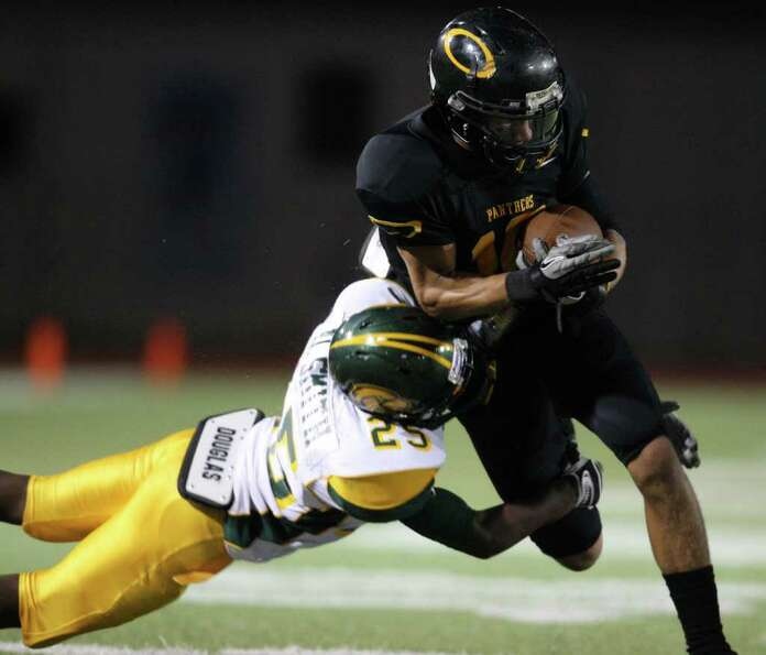 Klein Oak's Eugene Estes (right) is tackled by Klein Forest's Derrick Smith.