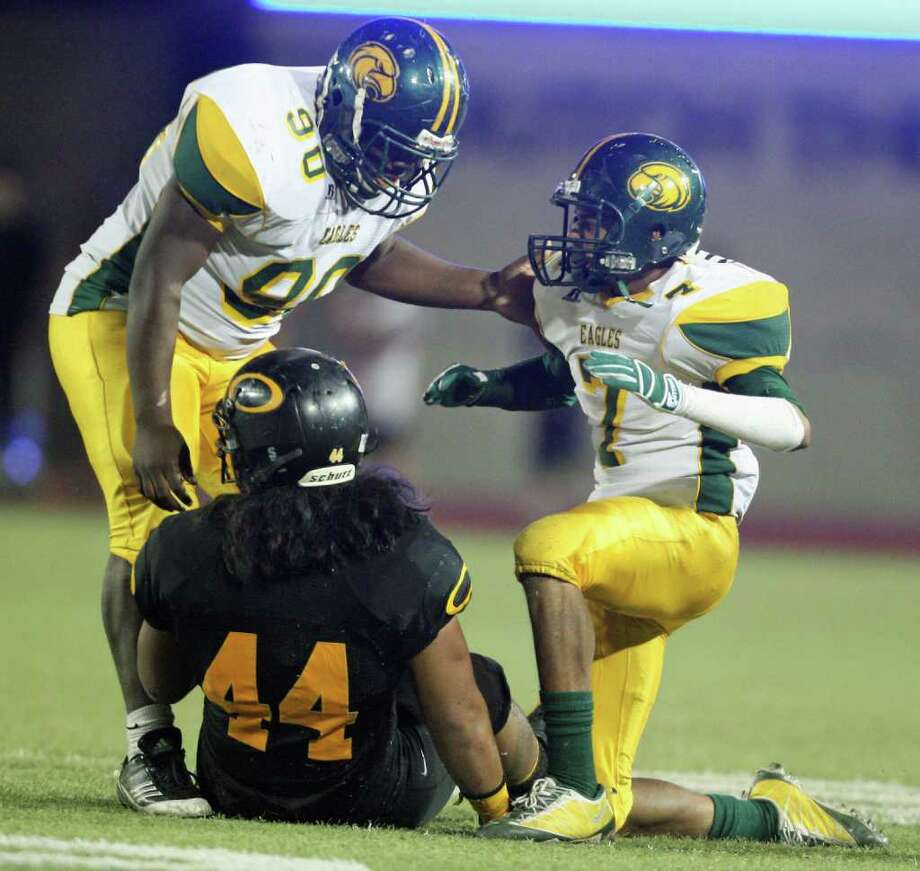 Klein Forest's DeAndre harris (right) celebrates his tackle of Klein Oak's EJ Fatu with teammate Ricky Holmes. Photo: Eric Christian Smith, For The Chronicle