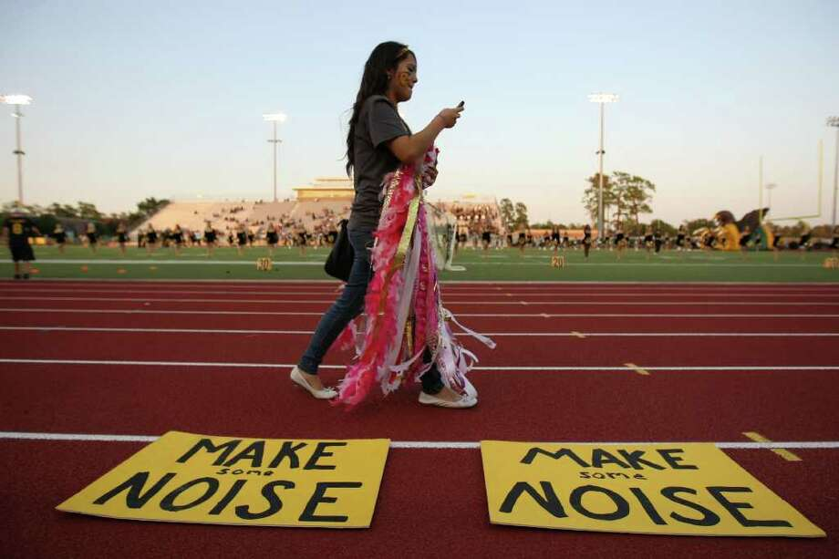 Klein Oak choir member Jessica Cervantes checks a text message while walking past spirit signs on the track before the Panthers' game against Klein Forest. Photo: Eric Christian Smith, For The Chronicle