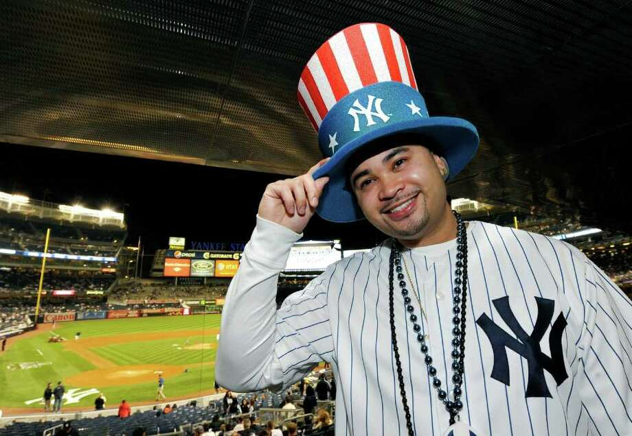 New York Yankees fan Nicholas Leetom, of Flushing, N.Y., shows off his Yankees hat he will wear during Game 1 of baseball's American League division series against the Detroit Tigers on Friday, Sept. 30, 2011, at Yankee Stadium in New York. (AP Photo/Kathy Kmonicek) Photo: Kathy Kmonicek / FR170189 AP