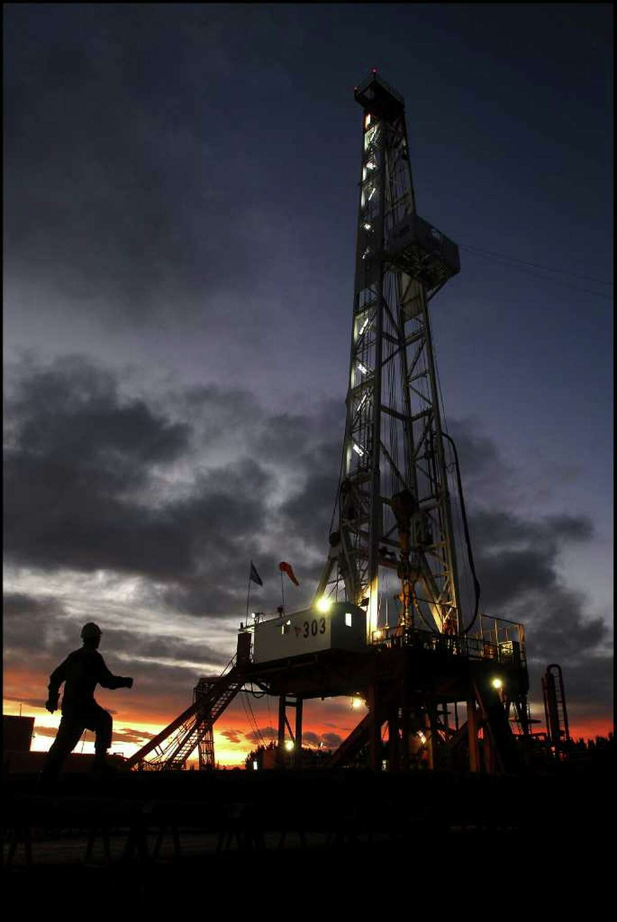 In this picture taken Nov. 26, 2009, an oil worker walks toward an oil drill in the province of Neuquen, Argentina. Argentina is promoting a new era of mining and energy production, welcoming billions of dollars in foreign investment to unlock huge new reserves of natural gas, oil, gold, lithium and other metals once thought to be unprofitable or out of reach. But there's one factor threatening this resource boom, something politicians and energy executives rarely mention: Huge amounts of fresh water will be required to extract these resources, in a country where water scarcity has long held back development and 16 percent of households still aren't connected to publicly treated drinking water. (AP Photo/Leonardo Petricio)