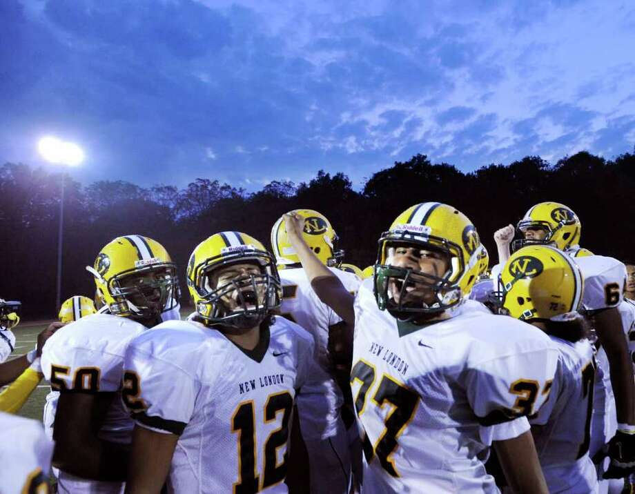 New London High School football players Nico Ramos, #12, and Taj Dickerson, # 37, and teammates at the start of High School football game between New London High School and Greenwich High School at Greenwich, Friday night, Sept. 30, 2011.  New London defeated Greenwich 51-33. Photo: Bob Luckey / Greenwich Time