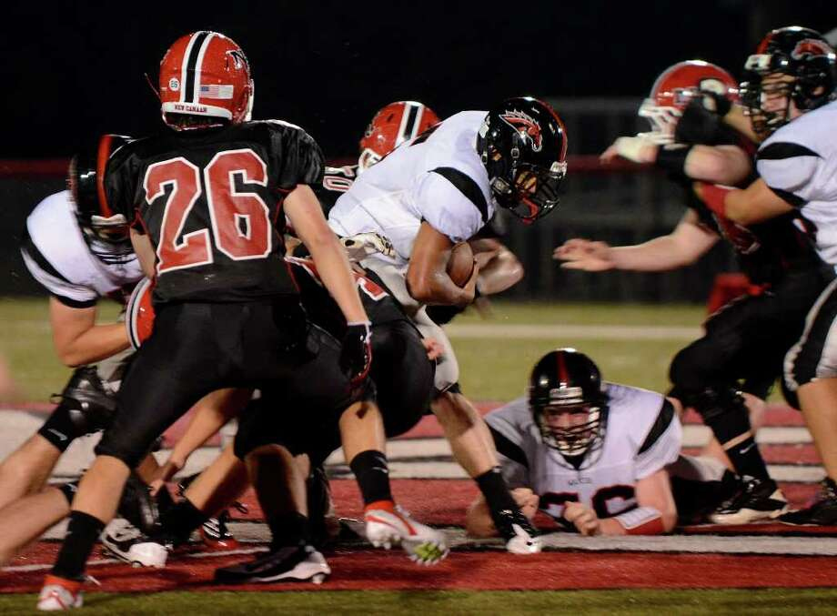Warde #5 Devin Lofton powers through the New Canaan defense, including #26 Jared Meichner as New Canaan High School hosts Fairfield Warde High School in varsity football action in New Canaan, CT on Friday, September 30, 2011. Photo: Shelley Cryan / Shelley Cryan freelance; Stamford Advocate freelance