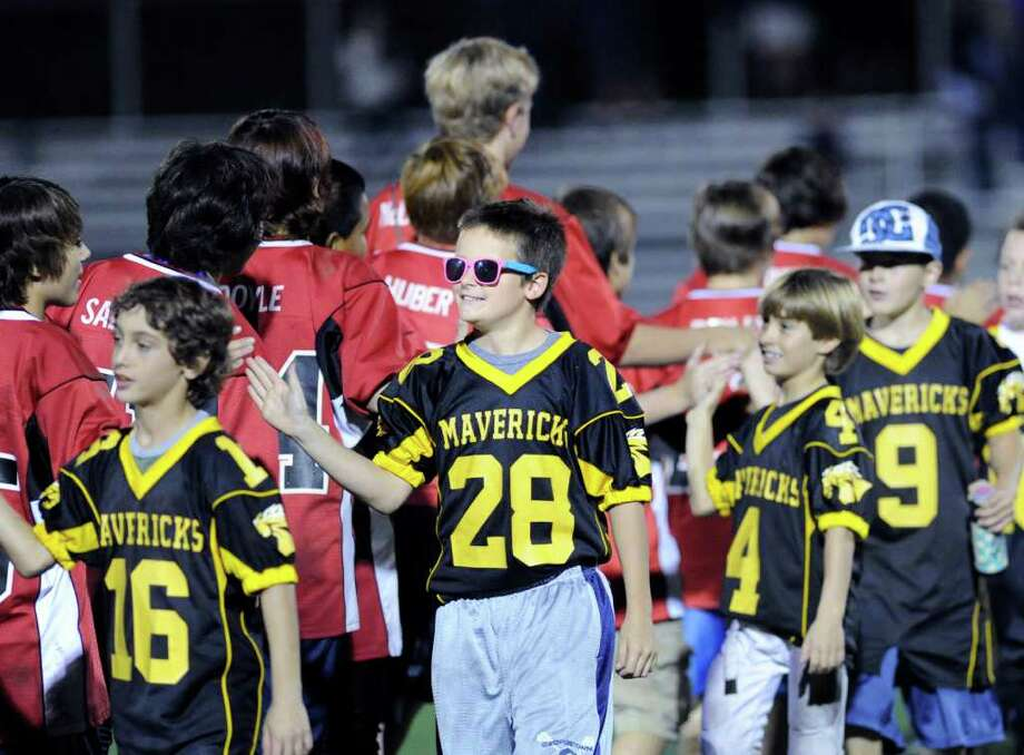 Wearing shades, Aengus Rosato, # 28 of the Mavericks youth football team, and his teammates were introduced during halftime of the High School football game between New London High School and Greenwich High School at Greenwich, Friday night, Sept. 30, 2011. Photo: Bob Luckey / Greenwich Time