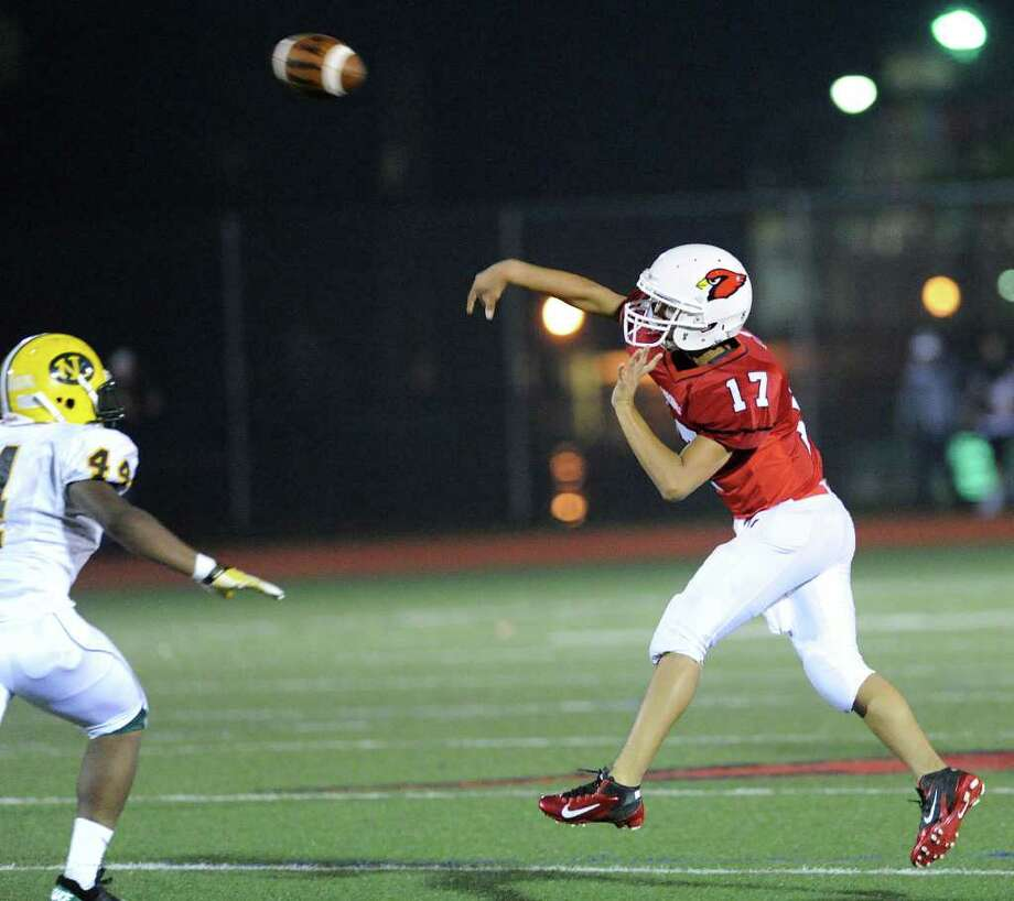 GHS quarterback Jose Melo, # 17, throws while being rushed by Dominic Snell, # 44 of New London High School during High School football game between New London High School and Greenwich High School at Greenwich, Friday night, Sept. 30, 2011.  New London defeated Greenwich 51-33. Photo: Bob Luckey / Greenwich Time