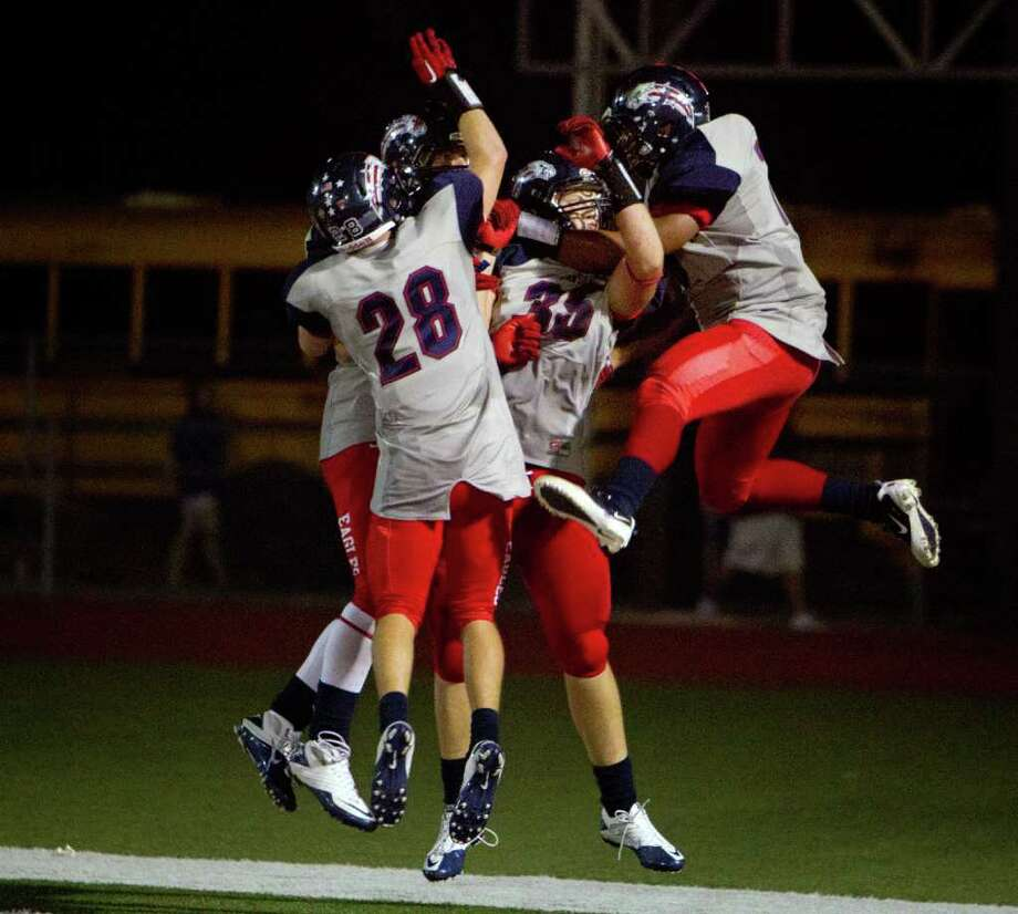 Dawson's Timothy Lundin (35) is mobbed by teammates after he returned an interception 68 yards for a touchdown against Friendswood during the fourth quarter. Photo: Smiley N. Pool, Houston Chronicle / © 2011  Houston Chronicle