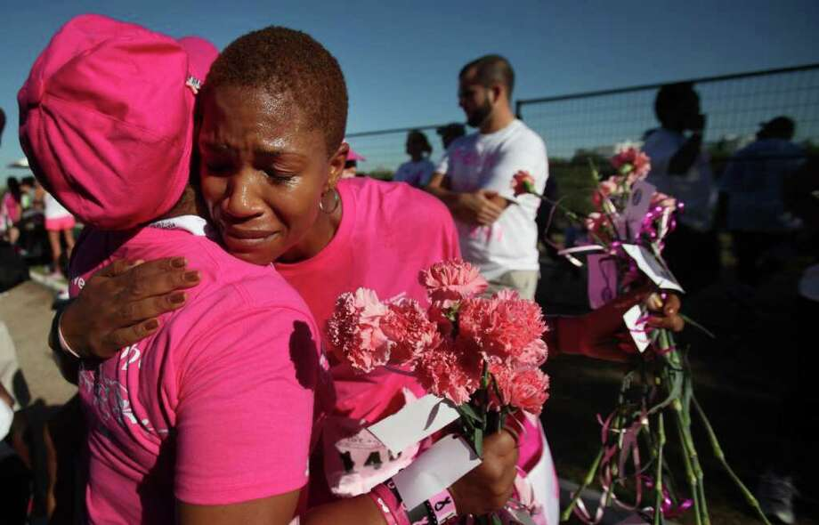 """In remission for four months"" says cancer survivor Nisha Kikunga, as her voice cracks and starts to cry and is embraced by fellow survivor Jackie Carroll, in remission for 9 years, after crossing the finish line at the Susan G. Komen Race for the Cure on Saturday, Oct. 1, 2011, in Houston.  The Komen Houston Race for the Cure is the largest footrace in Houston with more than 35,000 participants including 2,000 breast cancer survivors. More than $3.5 million dollars will be fundraised for breast cancer education, screening, treatment and cutting-edge research. Photo: Mayra Beltran, Houston Chronicle / © 2011 Houston Chronicle"