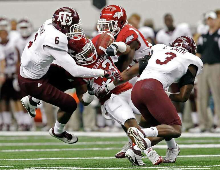 Arkansas running back Dennis Johnson (33) is brought down by Texas A&M defensive backs Desmond Gardi