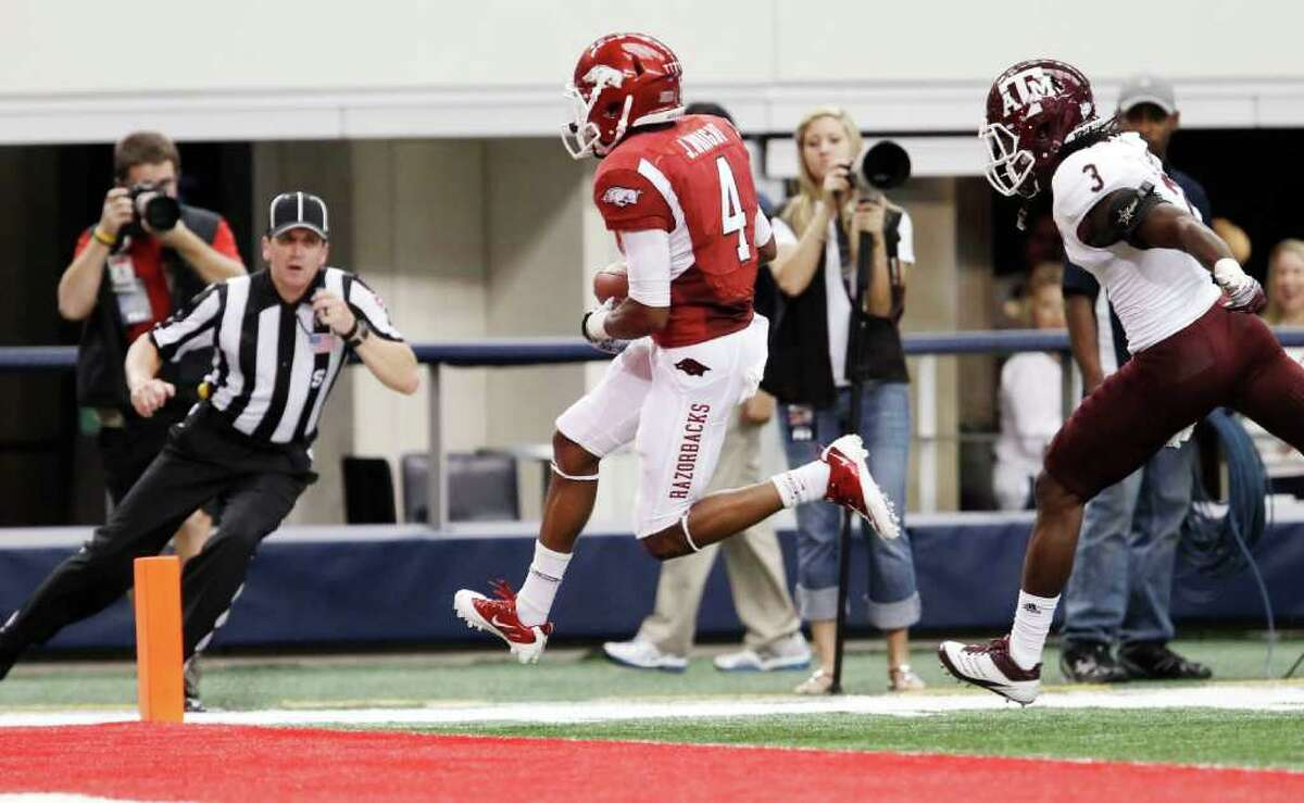 Texas A&M defensive back Lionel Smith (3) is unable to catch up to Arkansas wide receiver Jarius Wright (4) as he scores a touchdown during the first quarter of an NCAA college football game at Cowboys Stadium on Saturday, Oct. 1, 2011, in Arlington, Texas. (AP Photo/Brandon Wade)